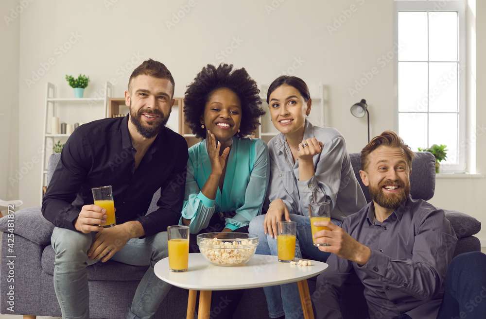 Fototapeta Young people having fun while spending weekend together. Millennial couples enjoying double date. Happy friends sitting on sofa at home, eating popcorn, drinking juice and watching sports game on TV