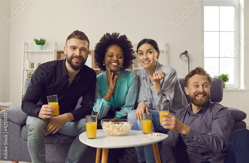 Obraz Young people having fun while spending weekend together. Millennial couples enjoying double date. Happy friends sitting on sofa at home, eating popcorn, drinking juice and watching sports game on TV - fototapety do salonu