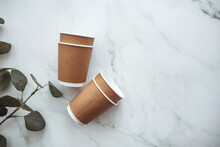 Set Of Disposable Coffee Nug And Table Ware, Eco Friendly. Disposable Cardboard Cup With Empty Space For Text On Gray Background. Take Out Coffee Or Delivery Service. Copy Space.
