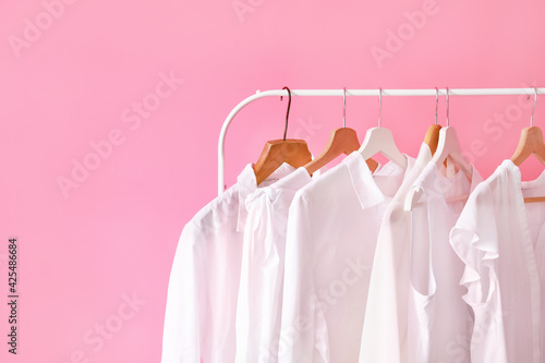 Rack with modern clothes in room