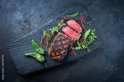 Traditional barbecue dry aged sliced wagyu roast beef with chili and red wine salt served as top view on a charred wooden board with copy space