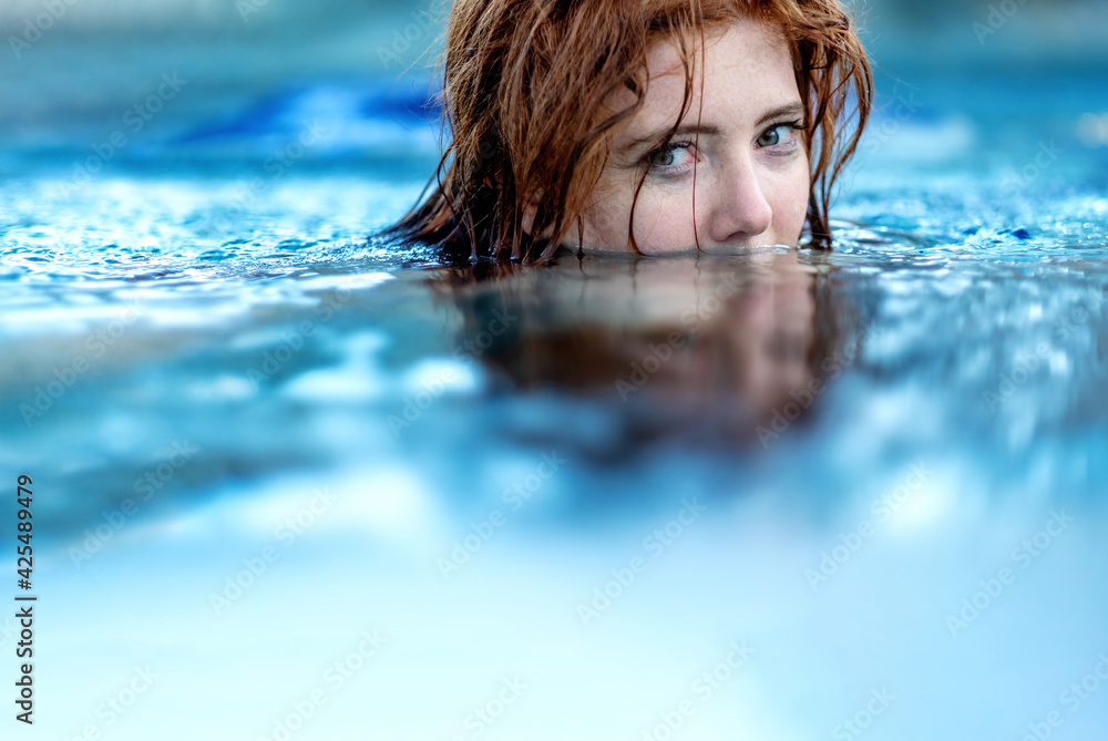 Fototapeta Portrait of young sexy woman with red hair, redhead swimming in the pool, head half submerged under water, copy space
