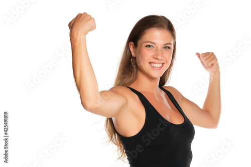 Photo a young beautiful smiling woman in a shirt showing her biceps