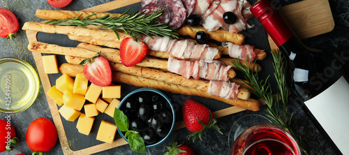 Fototapeta Board with grissini and snacks, and wine on black smokey table obraz