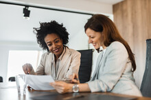 Portrait Of A Two Smiling Businesswomen Looking At Document.