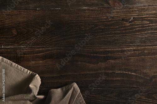tablero de madera vieja marrón oscuro con un objeto textil en una esquina.