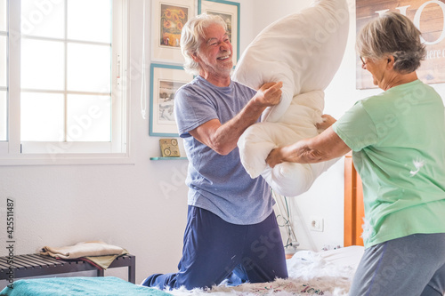 Obraz na plátne couple of two happy seniors having fun playing together on the bed at home fighting with pillows enjoying - pillows war indoors in the morning