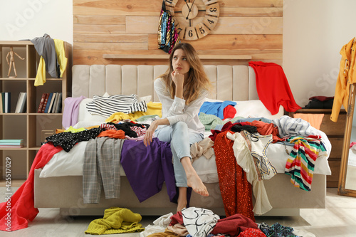 Obraz Young woman surrounded by different clothes in messy room. Fast fashion concept - fototapety do salonu