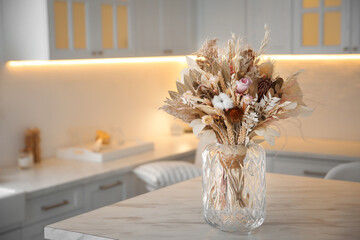Bouquet of dry flowers and leaves on table in kitchen. Space for text