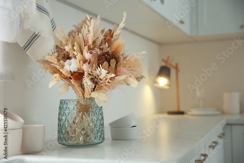 Obraz Bouquet of dry flowers and leaves on countertop in kitchen. Space for text - fototapety do salonu