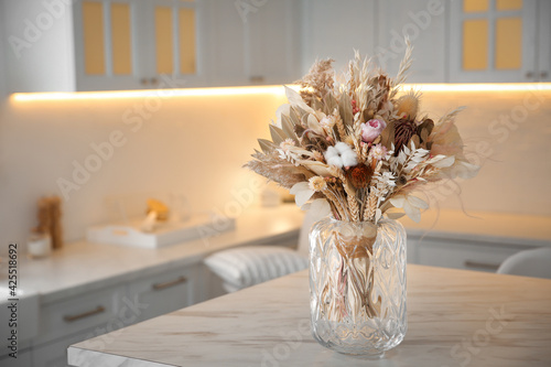Obraz Bouquet of dry flowers and leaves on table in kitchen. Space for text - fototapety do salonu