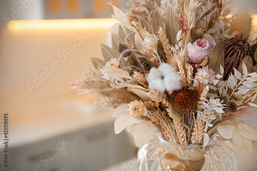 Obraz Bouquet of dry flowers and leaves in kitchen. Space for text - fototapety do salonu