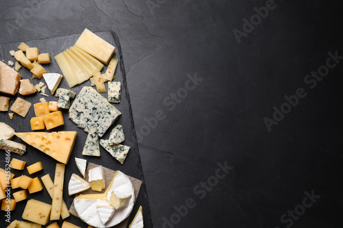 Photo Cheese plate on black table, top view. Space for text