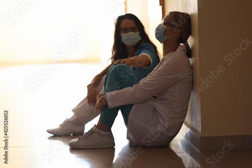 Obraz na plátně Tired women doctors are sitting in masks in corridor