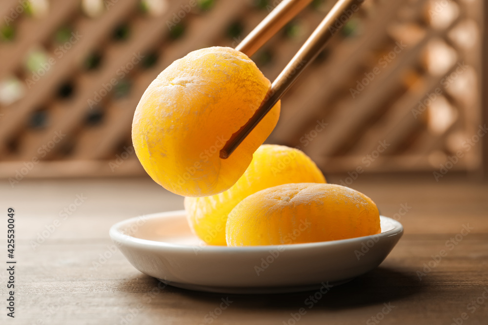 Fototapeta Taking delicious mochi from plate with chopsticks on wooden table. Traditional Japanese dessert