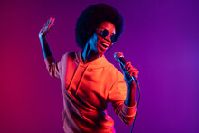 Photo Of Cheerful Singer Lady Hold Mic Open Mouth Wear Hoodie Eyeglasses Isolated Gradient Neon Background