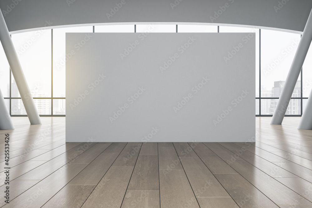 Fototapeta Grey partition with copyspace in sunny empty hall with grey columns, wooden floor and city view. 3D rendering, mockup