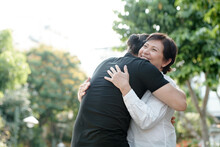 Cheerful Mature Woman Happy To See Her Adult Son After Quarantine Is Over, She Is Smiling And Hugging Him