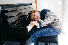 Frustrated Sad Boy With Glasses Playing Piano In Living Room. Lonely Child Learning To Play Music Instrument. Talented Upset Kid During Homeschooling Corona Virus Lockdown.