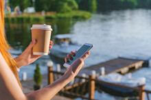 The Girl Is Holding A Smartphone With Coffee In Her Hands. In The Background Water Embankments With A Pleasure Boat.