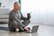 Senior man in sportswear sitting on fitness mat, using laptop