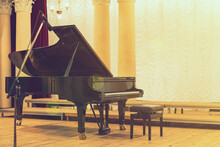 Grand Piano In Concert Hall. Piano Standing On Empty Stage. Opened Black Grand Piano With Stool On A Wooden Concert Stage. Toned