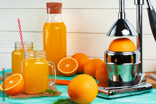 Glass of orange juice and cut oranges on table