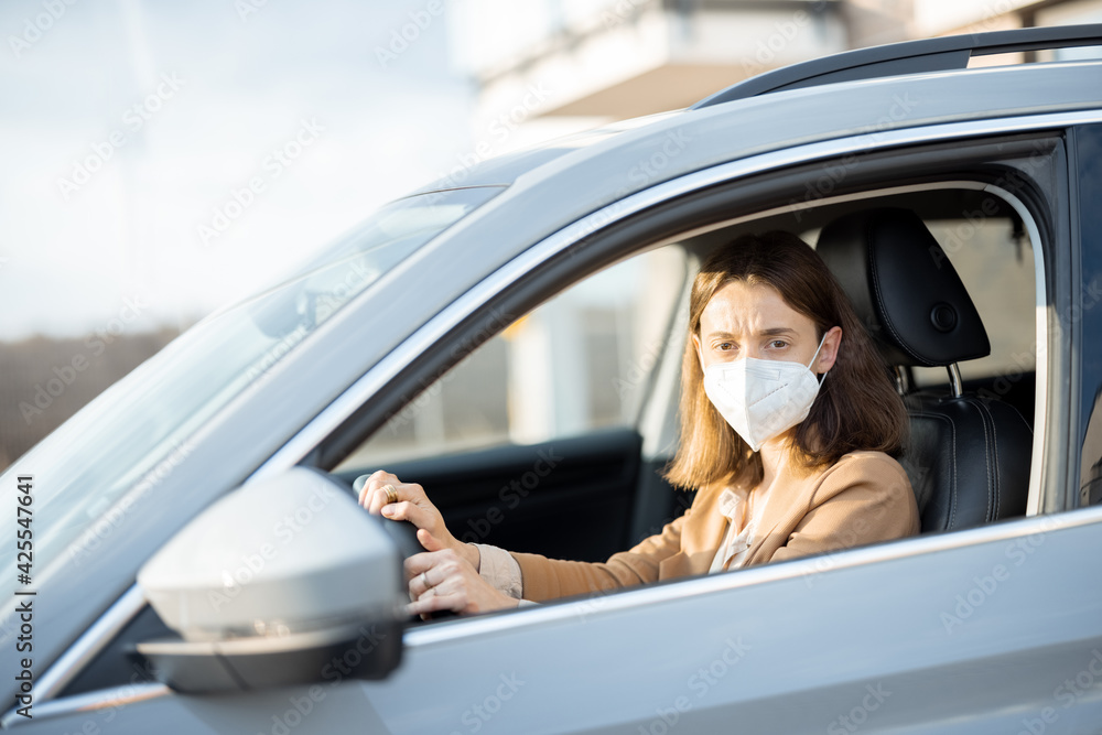 Fototapeta Young woman driving car with protective mask on her face. Looking worried at camera. Healthcare, virus protection, allergy protection concept.