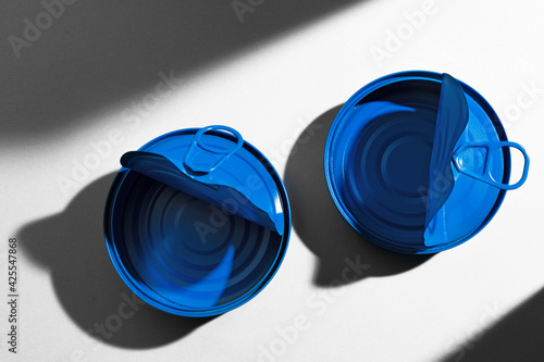 Painted blue opened tin can with ring on white background