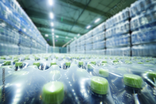 Obraz a huge industrial warehouse with plastic food wrap wrapped plastic bottles with carbonated drinks, water or beer. - fototapety do salonu