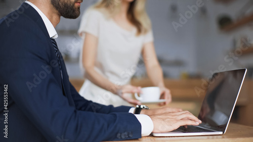 Fotografía cropped view of bearded businessman typing on laptop near woman with cup on blur