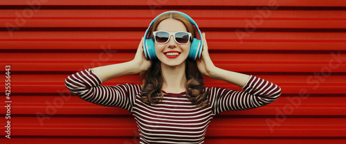 Vászonkép Portrait of happy young woman with wireless headphones listening to music on a r