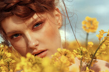 Young Fashion Model Portrait With Ginger Hair And Blue Eyes In Yellow Rapeseed Field