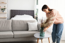 Woman Putting Vase With White Dried Pampas Grass On Table