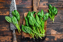 Young Baby Spinach Leaves On A Wooden Cutting Board. Dark Wooden Background. Top View