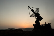 Creative Artwork Decoration. Silhouette Of Mobile Air Defence Truck With Radar Antenna During Sunset. Satellite Dishes Or Radio Antennas Against Evening Sky.