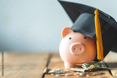piggy bank With Graduation Cap on old wood,Money saving concept. Fototapet