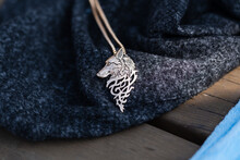 Pendant Wolf Head Necklace Golden Color Stainless Steel Shoot Outside In A Sunny Day Closeup. Selective Focus. High Quality Photo