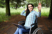 Woman In Wheelchair Waves Her Hand In Greeting