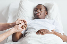 Close Up Of Caring Relative Holding Hand Of African-American Man Lying In Hospital Bed, Copy Space