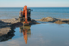 Large Tracked Excavator Digging And Cleaning Channel At The Coast