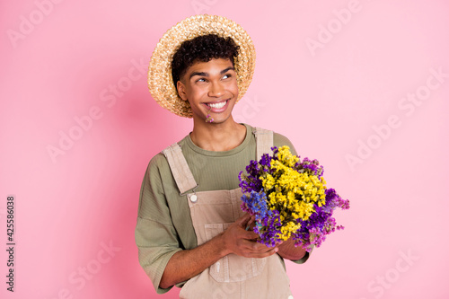 Fotografija Photo of villager guy hold bouquet flowers look empty space wear straw hat beige