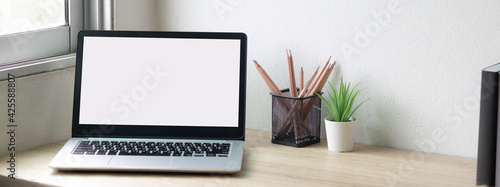Obraz Laptop computer with white blank screen on desk in workspace and copy space concept - fototapety do salonu