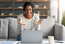 Smiling Black Woman In Headset Having Web Conference On Laptop At Home