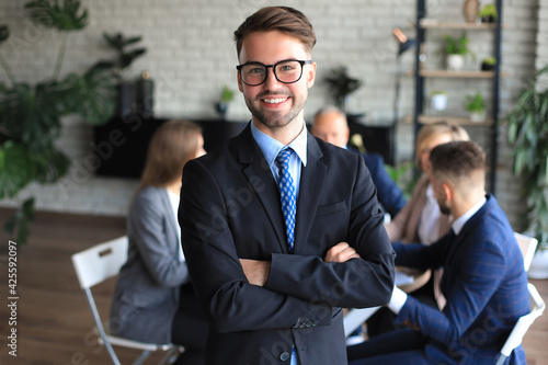 Obraz Businessman with colleagues in the background in office. - fototapety do salonu