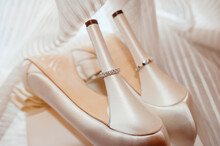 Silver Wedding Engagement Rings On Heels Of Bride Shoes With Dress In The Background