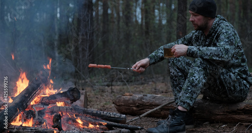 Fotografie, Obraz Adult man outdoors is cooking meal on fire