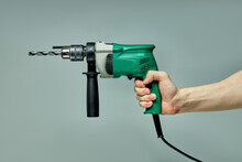Close-up Green Electric Hammer In Cropped Male Hands