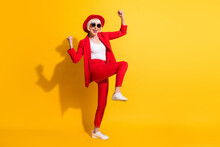 Full Length Body Size Photo Of Elder Woman In Red Suit Sunglass Gesturing Like Winner Isolated On Bright Yellow Color Background