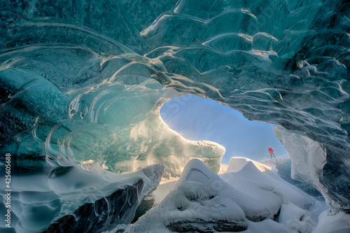 Fototapeta Man standing on edge of ice cave in Iceland